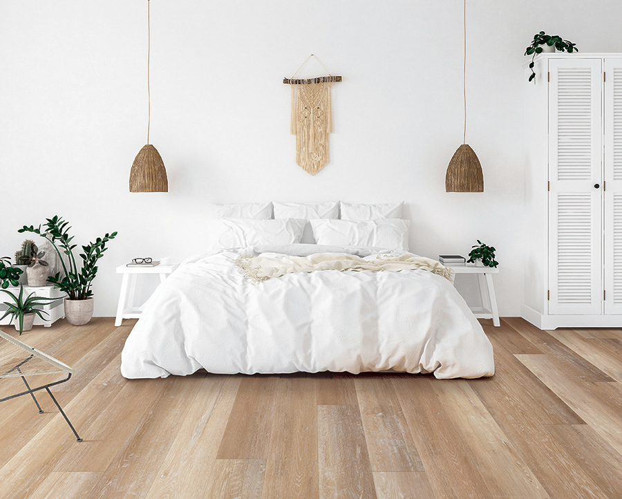 Scandinavian inspired bedroom with a comfy bed and light, white-washed luxury vinyl floors