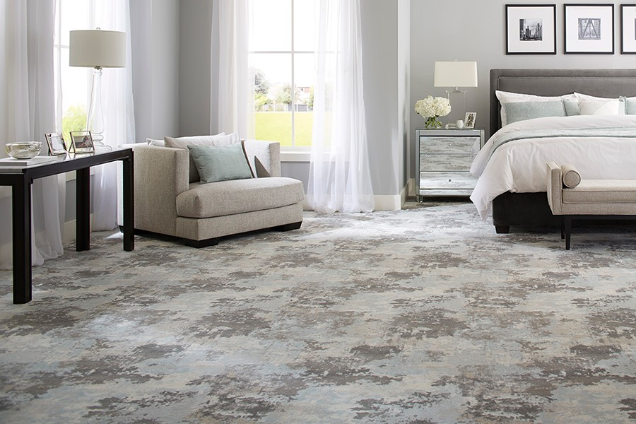 light colored master bedroom with distressed carpet